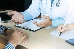 feche acima do paciente e da escrita do doutor algo na prancheta Wa Imagem de Stock