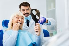 Feche acima do paciente satisfeito no escritório dental fotografia de stock royalty free