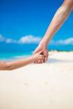 Feche acima do pai e da filha pequena que guardam-se as mãos na praia Fotos de Stock