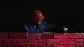 Feche acima do pedreiro industrial que instala tijolos do cimento na sala do darc estoque Conceito do auto-desenvolvimento críe filme