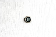 Feche acima do peephole da lente da porta na textura de madeira branca foto de stock royalty free