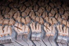 Feche acima do pneu 4x4 do passo fora da estrada, textura da picareta suja da roda Foto de Stock