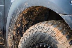 Feche acima do pneu 4x4 do passo fora da estrada, textura da picareta suja da roda Imagens de Stock