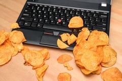 Feche acima do portátil aberto com as microplaquetas dispersadas no teclado Imagem de Stock Royalty Free