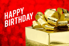 Feche acima do presente dourado com curva grande e da palavra do feliz aniversario em Fotografia de Stock Royalty Free