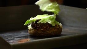 Feche acima do processo de cozinhar um hamburguer em uma cozinha aberta do fast food O cozinheiro frita bolos no fogão E filme