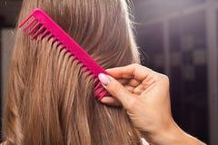 Feche acima do processo de escovar o cabelo fotos de stock