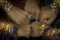 Feche acima do punho da mão dos amigos de meninos humanos que acautelam-se a faixa da amizade nos braços Expressão segura cel da  foto de stock