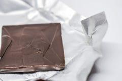 Feche acima do quadrado marrom escuro do chocolate rachado na folha de prata em um fundo branco imagens de stock royalty free