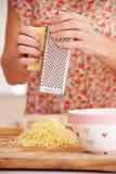 Feche acima do queijo grating da mulher na cozinha Foto de Stock