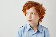 Feche acima do rapaz pequeno bonito com cabelo encaracolado vermelho e as sardas que olham de lado com interessado e o relaxado imagem de stock