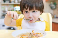 Feche acima do rapaz pequeno bonito que come a sopa Fotografia de Stock