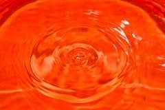 Feche acima do respingo da gota na água com fundo alaranjado Textura e projeto de superfície rippled brilhantes fotografia de stock royalty free