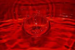 Feche acima do respingo vermelho da gota do SANGUE no sangue com fundo alaranjado Textura e projeto de superfície rippled brilhan imagens de stock