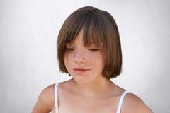 Feche acima do retrato da criança pequena freckled com penteado à moda curto, olhando para baixo ao sonhar sobre algo agradável b imagens de stock royalty free