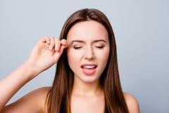 Feche acima do retrato da jovem mulher que arranca as sobrancelhas com pinça imagem de stock