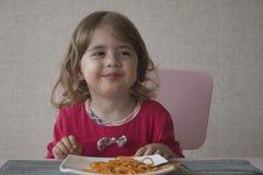 Feche acima do retrato da menina adorável que come os espaguetes e o sorriso Foto de Stock Royalty Free
