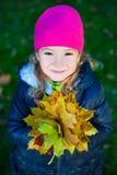 Feche acima do retrato da menina bonito com as folhas de bordo no autum Fotos de Stock Royalty Free