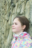 Feche acima do retrato da menina de sorriso em um blazer colorido com fundo das pedras Foto de Stock