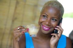 Feche acima do retrato da mulher de negócio afro-americana preta bonita e feliz nova no cabelo à moda na moda que fala no telefon foto de stock royalty free