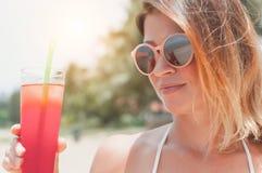 Feche acima do retrato da mulher feliz da forma nos óculos de sol com cocktail imagens de stock