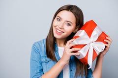 Feche acima do retrato da mulher feliz, nova, bonito que guarda o presente em r fotografia de stock