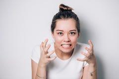 Feche acima do retrato da mulher irritada irritada nova que guarda as mãos no gesto furioso Fêmea nova no t-shirt branco imagens de stock royalty free