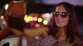 Feche acima do retrato da mulher moreno bonita nova nos óculos de sol que levantam fazendo as caras que tomam a utilização da fot video estoque