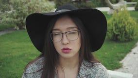 Feche acima do retrato da mulher séria e pensativa no chapéu negro e nos vidros exteriores filme