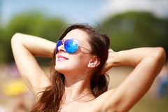 Feche acima do retrato da mulher 'sexy' bonita à moda nos vidros e com cabelo molhado em uma praia ensolarada com água azul foto de stock royalty free