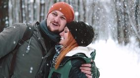 Feche acima do retrato Dan?a feliz dos pares dos pares, beijando, tendo o divertimento sob a queda de neve no movimento lento em  filme