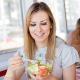 Feche acima do retrato de comer a menina loura bonito da jovem mulher bonita deliciosa da salada que tem o divertimento no restau Foto de Stock Royalty Free