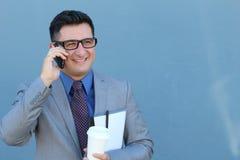 Feche acima do retrato de rir o homem de negócios novo na fala pelo telefone celular sobre o fundo azul foto de stock