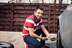 Feche acima do retrato de sorriso do homem de funcionamento e de pneus em mudança usando a chave, o jaque e ferramentas hidráulic fotografia de stock royalty free