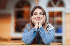 Feche acima do retrato de um assento louro bonito da cara da carne sem gordura da mão da menina exterior no café acolhedor na cid Imagem de Stock Royalty Free