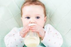 Feche acima do retrato de um bebê com uma garrafa de leite que encontra-se em uma cobertura feita malha verde Fotografia de Stock Royalty Free