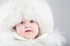 Feche acima do retrato de um bebê doce em um chapéu forrado a pele branco Fotos de Stock