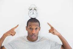 Feche acima do retrato de um homem que aponta no despertador sobre sua cabeça Imagem de Stock
