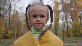 Feche acima do retrato de uma criança da menina da jovem criança que sorri na câmera A menina veste o revestimento amarelo em um  vídeos de arquivo