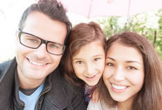 Feche acima do retrato de uma família de três feliz. Imagem de Stock