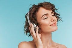 Feche acima do retrato de uma jovem mulher deleitada que escuta foto de stock royalty free