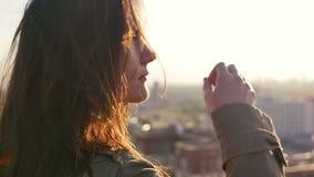 Feche acima do retrato de uma menina que está no telhado e aprecie a vista da cidade Movimento lento vídeos de arquivo