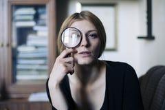 Feche acima do retrato de uma mulher bonita com uma lente de aumento de vidro Fotografia de Stock Royalty Free