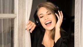 Feche acima do retrato de uma mulher de canto nos fones de ouvido Canta cedo na manhã em casa Foto de Stock
