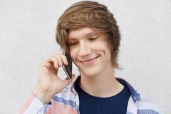 Feche acima do retrato do adolescente considerável com penteado na moda, sorrindo delicadamente tendo ondulações nos mordentes, c fotografia de stock