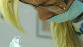 Feche acima do retrato do doutor fêmea nos vidros com desgaste protetor do trabalho Cara fêmea na máscara médica Cosmetologist ou filme