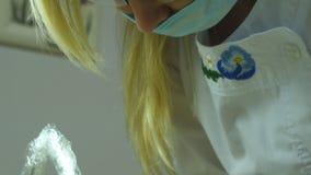 Feche acima do retrato do doutor fêmea nos vidros com desgaste protetor do trabalho Cara fêmea na máscara médica Cosmetologist ou vídeos de arquivo
