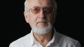 Feche acima do retrato do homem superior em uma camisa branca no fundo preto filme