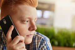 Feche acima do retrato do indivíduo elegante com o cabelo vermelho que tem sardas em sua cara que fala sobre o telefone ao situar fotos de stock royalty free