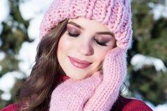 Feche acima do retrato do inverno de uma mulher de sorriso nova em um chapéu cor-de-rosa Foto de Stock